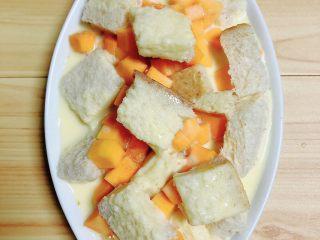 南瓜烤吐司布丁,蛋液与切片和南瓜融合在一起。提前预热烤箱,180度预热5分钟。