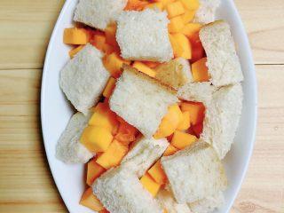 南瓜烤吐司布丁,将切片面包块和南瓜块放入烤盘中。