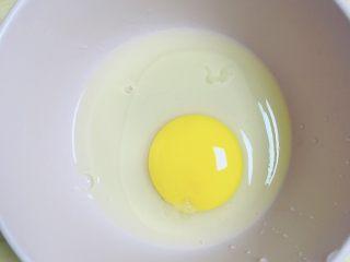 红提芝士烤吐司布丁,取一只碗,打入一个鸡蛋。