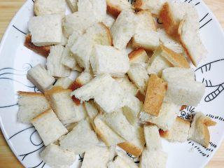 红提芝士烤吐司布丁,将面包切片切小块儿待用。