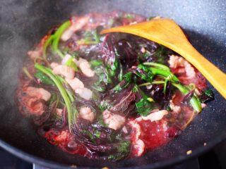 蒜香肉片炒苋菜,锅中看见苋菜断生,汤汁变成红色的时候。