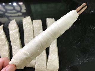 烤面筋,准备好两根筷子,取一条面筋,切面朝上,一头用筷子夹住后用手慢慢抻开面团,一手转动筷子让面团缠在筷子上,一层错开压住一层,收口处捏紧,防止脱落。