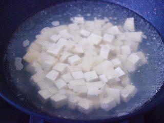 肉末番茄烩豆腐,把豆腐用刀切成小丁,锅中倒入适量清水煮沸后,放入少许盐,放入豆腐进行焯水,豆腐煮2分钟左右,捞出沥干水分备用。