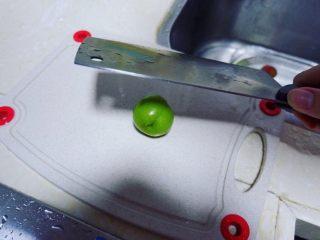 潮汕毂(ka)蜡李,像拍蒜头一样拍碎李子。把李子放在砧板上,用刀背一面拍下,圆溜溜的李子可能会溜走,因此还需要掌握好这个力度。