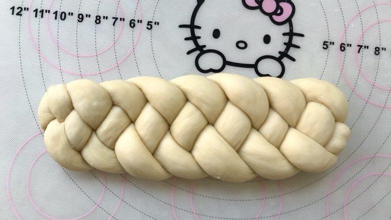 烫种芝麻辫子面包,搓成4根长条后,编成辫子,两头捏紧