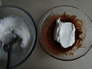 可可味小蛋糕卷,用刮刀把1/3打发好的蛋白霜到可可蛋黄糊里,右手拿着刮刀,从底部划J字翻拌,左手逆时针转动打蛋盆