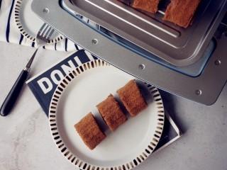 可可味小蛋糕卷,烘烤结束,把蛋糕取出,晾凉3分钟,再倒扣在另一张干净的油纸上