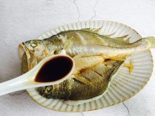 广式清蒸黄鱼,倒掉汤汁夹出葱段不要,再淋入一勺蒸鱼豉油