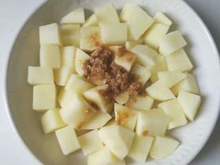 香酥排骨蒸土豆,把刚才排骨料理碗里的剩余酱料和蒜蓉倒进土豆里