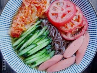 朝鲜冷面,放入黄瓜丝,泡菜,番茄,火腿装饰,撒上少许白芝麻即可。