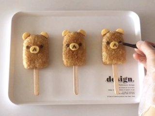 轻松熊雪糕饭团 ,椭圆芝士片放在饭团中间,用海苔剪出眼睛、鼻子和嘴,借助镊子放到相应的位置上,完成!