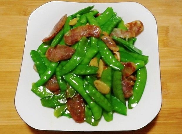 荷兰豆炒香肠,找个清爽的盘子装,颜色搭配很重要,任何一道菜根据颜色搭配,这样才能显示出菜肴的价值。