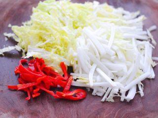 天鹅蛋白菜海鲜小炒,把大白菜用刀切成丝,红椒也切成丝。