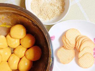 南瓜糯米薯片饼,将南瓜糯米面团揉成一个个小圆球。准备好了薯片和白芝麻。