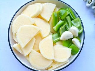 好吃到哭的茄汁土豆片,土豆去皮切片,泡水10分钟清洗掉淀粉。青椒切小块,大蒜拍扁。