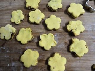 南瓜糯米夹心饼,按压后,脱模成,小个的花朵夹心饼坯,当中点上黑芝麻