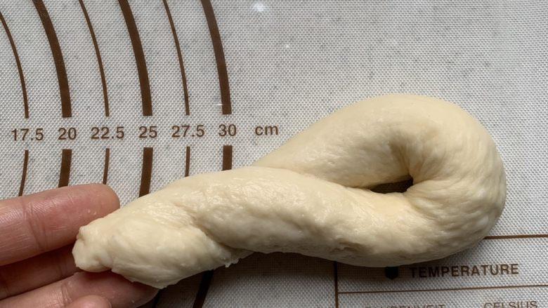 老式面包,对折,一手抓住两头,一手卷上劲。将尾部塞入另一端的孔里。