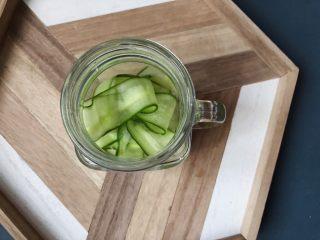 夏日清爽黄瓜水🥒高颜值清暑解渴神水,把削好的黄瓜片放入玻璃器皿。