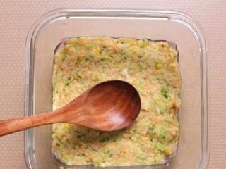 西兰花玉米鸡肉糕,倒入鸡肉泥蔬菜泥,用勺子压实抹平