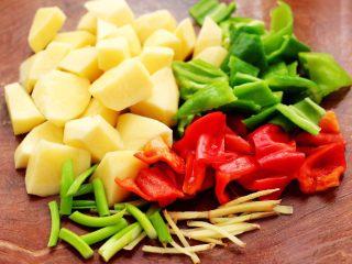 鸭腿烧双椒土豆,土豆去皮后洗净,用刀切成菱形块,青红椒切成薄片,葱姜切丝。