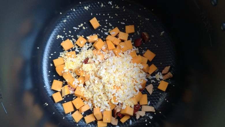 营养丰富+藜麦南瓜粥,南瓜和大米、小米倒入锅中。