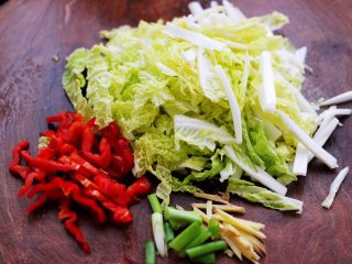 鸡胗爆炒大白菜,把大白菜洗净后用刀切成丝,红椒和葱姜切丝。
