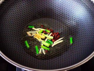 鸡胗爆炒大白菜,锅烧热后,倒入15克花生油烧热,小火慢慢炸香花椒后,大火爆香葱姜丝。