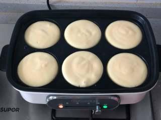 日式舒芙蕾松饼,多功能锅用六圆盘预热后,刷一层油,往圆盘里舀入一大勺面糊。用不粘平底锅也可以,面糊会自然形成圆形。