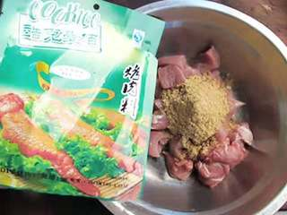 孜然羊肉串,把肉丁放入盆里,倒入25克的孜然烤肉料