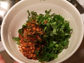 凉拌青笋豆干,碗里放入葱花,香菜,盐,花椒粉,辣椒粉,蒜泥,芝麻。