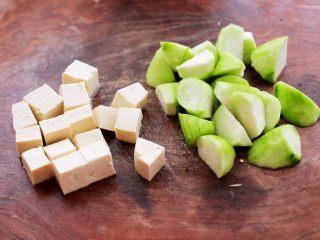 丝瓜花蛤炖豆腐,丝瓜去皮后切成滚刀块,豆腐切小方块。
