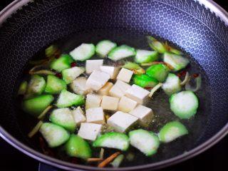 丝瓜花蛤炖豆腐,大火煮沸后,放入焯水的豆腐。