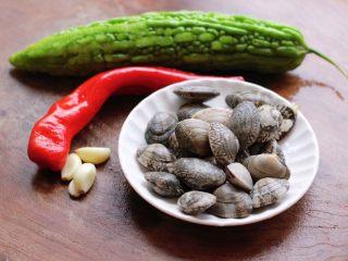 苦瓜辣炒花蛤,先把食材备齐,大蒜去皮,把花蛤提前用淡盐水浸泡浸泡吐沙后洗净备用。