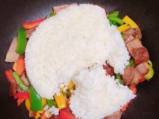 彩椒肘花肉炒饭(5分钟快手炒饭),放入米饭,改为中小火,用铲子将米饭分隔开,追减打散米粒,翻炒均匀。