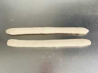 猪肉茴香馅儿饺子🥟,揉均匀的面团平均分成两份,取其中的一份揉搓成长条形。