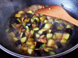 茄丁双椒炒肉丁,大火快速翻炒至茄丁断生变软的时候,加入少许清水。
