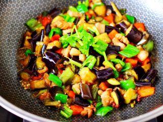 茄丁双椒炒肉丁,撒上香菜段,即可关火。