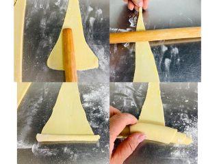 牛角酥,取一个面剂低部在轻轻擀压一下,在把擀面棍横过来向前擀压一遍,从底部向上卷起。