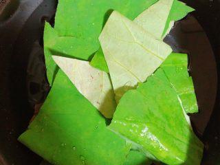 鲜荷叶百合莲子粥(清热解暑),锅中烧水,放入荷叶煮开锅后,小火儿熬5分钟。