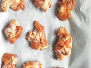 比外卖还好吃的秘制烤翅根,在烤盘上铺一张干净的油纸,把腌制好的翅根均匀的放在烤盘上。