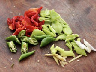 杏鲍菇虾仁三椒小炒,把青椒和红椒,杭椒用刀切块,葱姜切丝。
