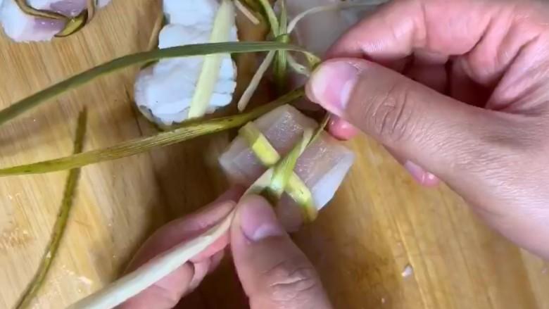 粽香五花肉,用粽丝将五花肉绑起来