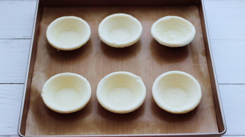 蓝莓黄桃酸奶蛋挞,把冷冻的蛋挞皮室温解冻后,放入烤盘里。