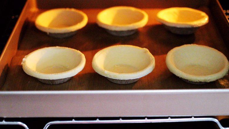 蓝莓黄桃酸奶蛋挞,烤箱200度预热10分钟后,把蛋挞皮放入烤箱中层。