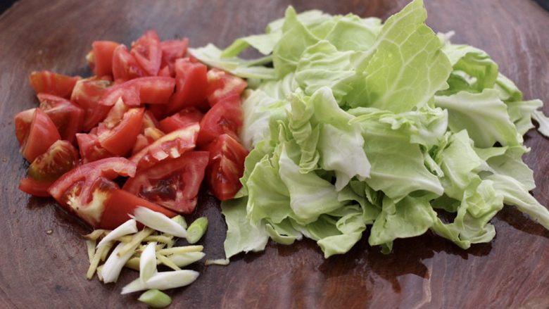 包菜番茄花蛤汤,把<a style='color:red;display:inline-block;' href='/shicai/ 3511'>包菜</a>用手撕成片,番茄用刀切成块,葱姜切丝。
