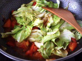 包菜番茄花蛤汤,大火继续翻炒至番茄变软后,放入撕片的包菜,大火继续翻炒片刻。