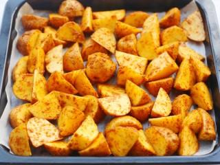 好吃到吮指的烤薯角,处理好的土豆放入铺好油纸的烤盘中。