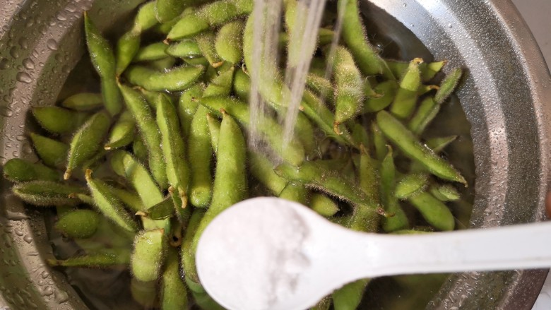 香辣毛豆,把毛豆放进盐水里面搓洗,这样比较容易洗净毛豆壳上的绒毛,然后用清水冲洗几次,洗好后控干水分。