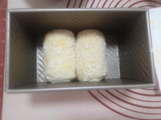 酸奶菠萝芝士土司,把两个面卷正面超上放到土司膜中进行二发,大概经过一个半小时到两个小时,面团发到离满膜还有1.5厘米的状态