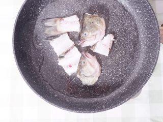柠檬酸汤鲈鱼,热锅倒油,将鱼头鱼骨煎至焦黄